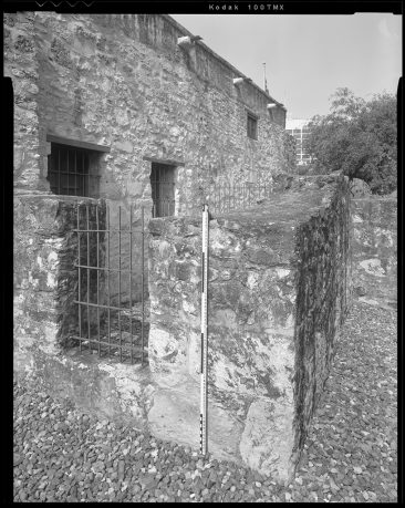 TX-318-A-13 North facade and wall looking southwest with scale